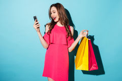 Smiling young brunette woman holding shopping bags chatting by phone. Stock Photo