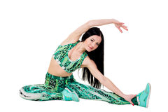 Smiling young brunette woman with long hair sitting does stretch Royalty Free Stock Photography