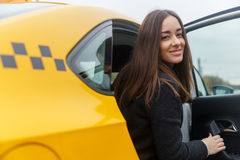 Smiling young brunette woman posing from classic yellow taxi Stock Image