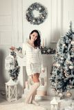 Smiling young brunette woman standing near fir tree in Christmas Royalty Free Stock Images