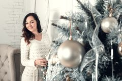 Smiling young brunette woman standing near fir tree in Christmas Stock Photo