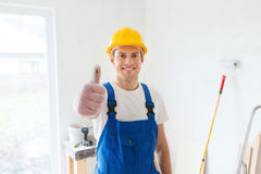 Smiling young builder in hardhat showing thumbs up Royalty Free Stock Image
