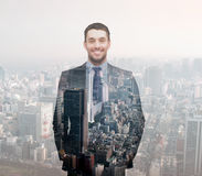 Smiling young buisnessman over city background Royalty Free Stock Image