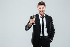 Smiling young businesman with glass of champagne standing and celebrating. Over white background Royalty Free Stock Image
