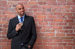 Smiling young business man drinking wine stock photo