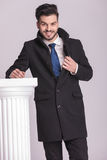Smiling young business man fixing his coat Royalty Free Stock Images