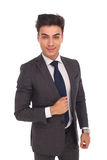 Smiling young business man holding his jacket's collar Royalty Free Stock Image