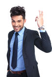 Smiling young business man making a greeting hand gesture Royalty Free Stock Images