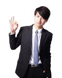 Smiling young business man with okay gesture Stock Image