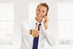 Smiling young business man with a phone Stock Photography