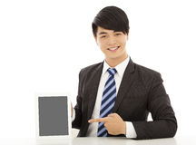 Smiling young business man show a tablet Royalty Free Stock Photography