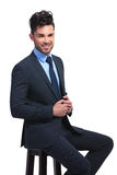 Smiling young business man sitting on a stool Stock Photo