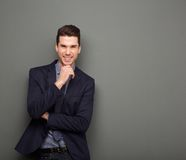 Smiling young business man standing with hand to chin Royalty Free Stock Photography
