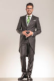 Smiling young business man standing on studio background. Royalty Free Stock Photography