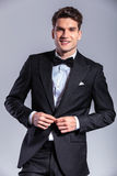 Smiling young business man unbuttoning his tuxedo Stock Image