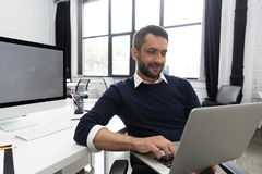 Smiling young business man using laptop. In an office Stock Images