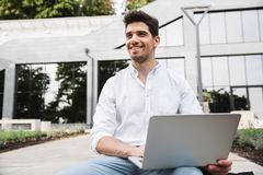 Smiling young business man working on laptop computer. While sitting outdoors royalty free stock photos