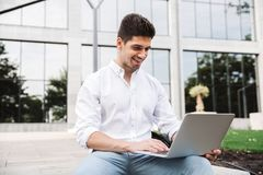 Smiling young business man working on laptop computer. While sitting outdoors stock image