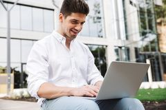 Smiling young business man working on laptop computer. While sitting outdoors royalty free stock photo