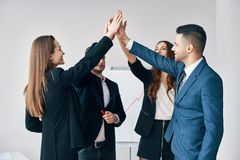 Smiling young business people giving high five to each other in office royalty free stock photography