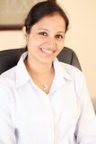 Smiling young business woman. At work place Stock Image
