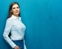 Smiling young business woman against blue wall. Royalty Free Stock Photo
