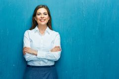 Smiling young business woman against blue wall. White shirt dresed Stock Image