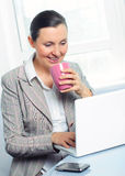 Smiling young business woman with cup using laptop Stock Image
