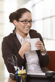 Smiling young business woman drinking co Stock Photos