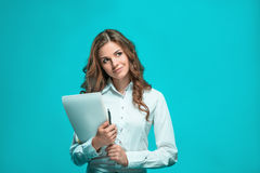 The smiling young business woman with pen and tablet for notes on blue background Stock Photo