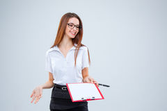 The smiling young business woman with pen and tablet for notes on gray background Stock Image