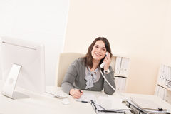 Smiling young business woman on phone at office Stock Photos