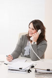 Smiling young business woman on phone at office Royalty Free Stock Images