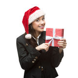 Smiling young business woman in santa hat holding red gift Stock Images