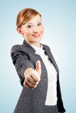 Smiling young business woman showing OK sign. To camera. Blue gradient as background Stock Images