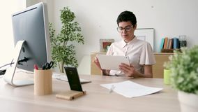 Smiling young business woman using her digital tablet while working in the office. stock video
