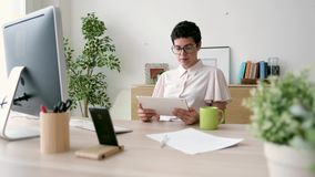 Smiling young business woman using her digital tablet while working in the office. stock footage