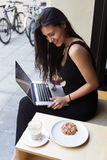 Smiling young business woman using laptop computer for distance work while sitting in coffee shop in fresh air during breakfast. Happy latin female speaks on Stock Photography