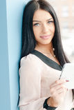 Smiling young business woman using tablet PC while standing relaxed near window at her office Stock Photography