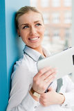Smiling young business woman using tablet PC while standing relaxed near window at her office Royalty Free Stock Photo