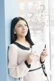 Smiling young business woman using tablet PC while standing relaxed near window at her office Stock Image