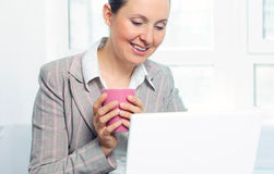 Smiling Young Business Woman With Cup Using Laptop Stock Images