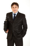 Smiling young businessman with briefcase in hand Stock Photos