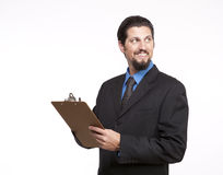 Smiling young businessman with a clipboard looking away Stock Photos