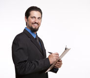 Smiling young businessman with a clipboard making notes Royalty Free Stock Photos