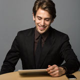 Smiling young businessman. With computer tablet, studio background Stock Image