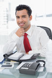 Smiling young businessman with diary sitting at office Royalty Free Stock Photo