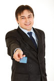 Smiling young businessman giving credit card Stock Photography