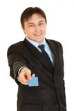 Smiling young businessman giving credit card. Stock Photo