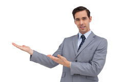 Smiling young businessman giving a presentation with his hands Royalty Free Stock Photo